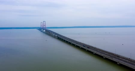 madura : Beautiful aerial hyperlapse of Suramadu strait and the Suramadu bridge from a drone flying from left to right in Surabaya, East Java, Indonesia. Shot in 4k resolution