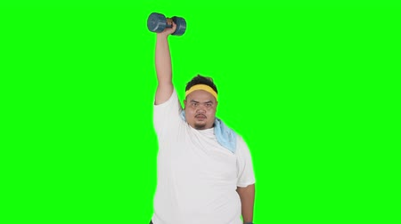 túlsúly : Obese young man workout in the studio with dumbbells while looking at the camera. Shot in 4k resolution with green screen background Stock mozgókép