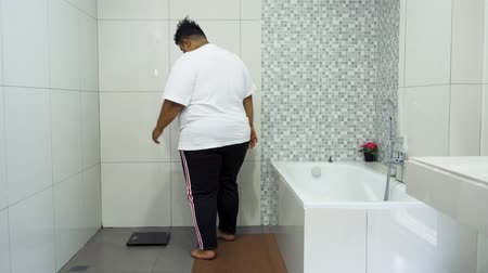 kaybetmek : Overweight man measuring his weight with a scale on the morning in the bathroom at home. Shot in 4k resolution