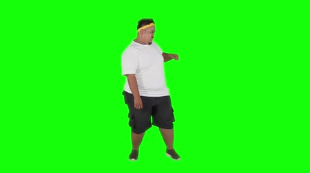 fulllength : Slow motion of overweight young man punching something in the studio. Shot in studio with green screen background