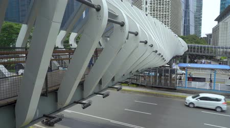 sudirman : JAKARTA, Indonesia - March 21, 2019: Pedestrian walking on the modern futuristic bridge above Sudirman highway. Shot in 4k resolution