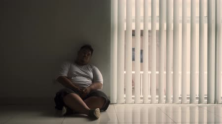 мигрень : Silhouette of sad overweight man sitting near the window at home. Shot in 4k resolution
