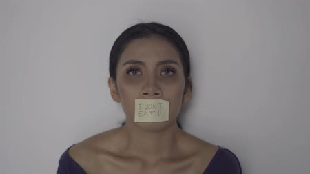 nervosa : Skinny anorexic woman with text of I Wont Eat on her mouth. Shot in 4k resolution