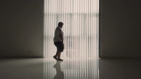 упитанность : Silhouette of stressful overweight man walking near the window at home. Shot in 4k resolution