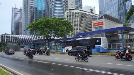 indonesia : JAKARTA, Indonesia - March 21, 2019: Sudirman street view with Transjakarta bus stop and fast moving vehicles. Shot in 4k resolution Stock Footage