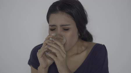 indonesian : Thirsty skinny anorexic woman drinking a glass of water. Shot in 4k resolution