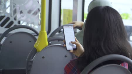 interior subway : Back view of young woman using smartphone while sitting in the bus. Shot in 4k resolution