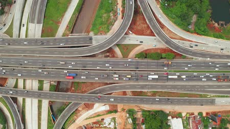 interchange : Top down view of Depok Antasari toll road intersection from a drone flying from left to right. Shot in 4k resolution Stock Footage
