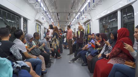 rapid transit : JAKARTA, Indonesia - March 26, 2019: Passengers using mobile phone in Mass Rapid Transit (MRT) subway train Jakarta. Shot in 4k resolution