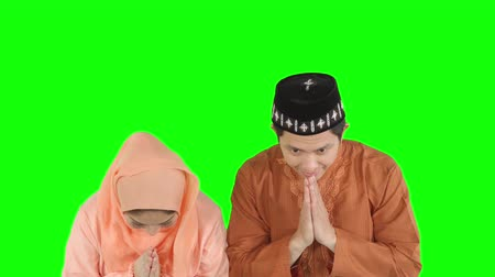 perdão : Attractive muslim couple showing a greeting hands gesture and smiling to each other in the studio Vídeos