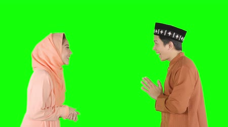 для взрослых : Happy muslim couple giving a greeting hands gesture for forgiving each other in the studio. Shot in 4k resolution with green screen background