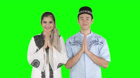 saudação : Attractive young muslim couple smiling at the camera while showing greeting hands gesture. Shot in 4k resolution with green screen background