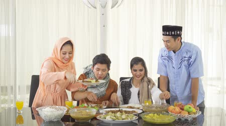 mladé ženy : Group of young attractive muslim people eating Indonesian traditional foods during break the fast together in dining room at home. Shot in 4k resolution Dostupné videozáznamy