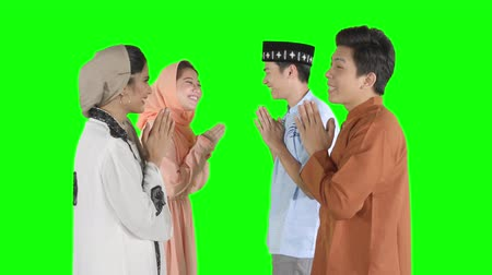 saudação : Group of happy young muslim people wearing islamic clothes and forgiving each other by showing a greeting hands gesture in the studio. Shot in 4k resolution with green screen background Vídeos