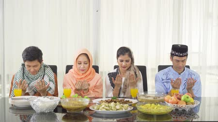 asian and indian ethnicities : Group of young muslim people praying together before eating on the table in dining room at home. Shot in 4k resolution