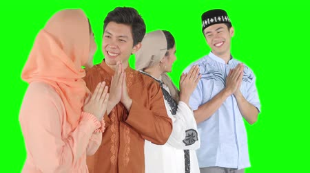 saudação : Group of attractive young muslim people showing a greeting hands gesture for forgiving and congratulate. Shot in 4k resolution with green screen background