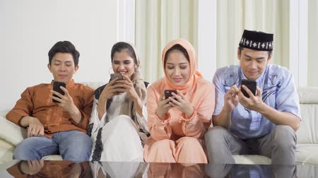 головной платок : Group of young muslim people using a mobile phone while sitting on the sofa in the living room at home. Shot in 4k resolution