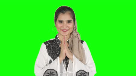 perdão : Beautiful young muslim woman showing a greeting hand gesture of muslim culture in the studio. Shot in 4k resolution