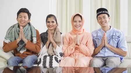 saudação : Group of attractive young muslim people showing a greeting hands gesture while smiling at camera and sitting on the sofa at home. Shot in 4k resolution