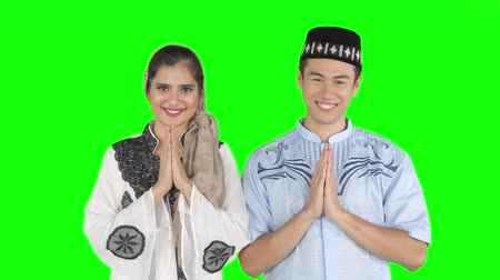 véu : Young muslim couple showing a greeting hands gesture while smiling at the camera in the studio. Shot in 4k resolution with green screen background