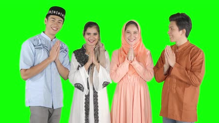 для взрослых : Group of young muslim people with greeting hands gesture for forgiving each other in the studio. Shot in 4k resolution with green screen background