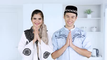 perdão : Attractive young muslim couple smiling at the camera and showing greeting hands gesture while wearing islamic clothes during ramadan at home. Shot in 4k resolution