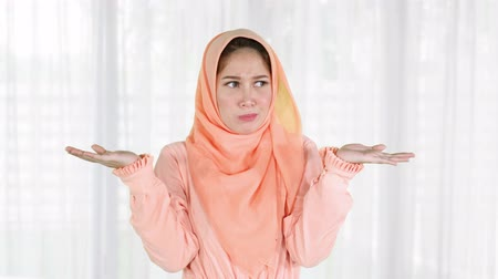 nejistota : Thoughtful pretty young muslim woman looks confused and shrugging her shoulder while wearing islamic clothes at home. Shot in 4k resolution