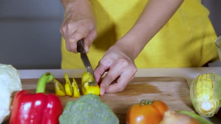 ブロッコリー : Woman hands slicing vegetables on chopping board for cooking in the kitchen at home