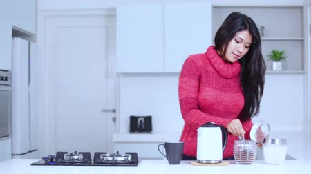 grzejnik : Attractive young woman making hot coffee while wearing winter clothes in the kitchen at home Wideo