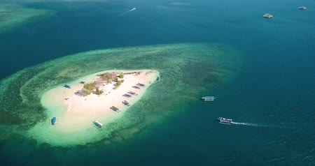 посетитель : Beautiful aerial landscape of Gili Kedis Island with turquoise water, white sand, and tourism boats in Lombok near Bali, Indonesia.Shot in 4k resolution from a drone flying from left to right Стоковые видеозаписи