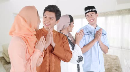 saudação : Group of young Asian muslim people wearing islamic clothes and congratulate Eid Mubarak day at home. Shot in 4k resolution