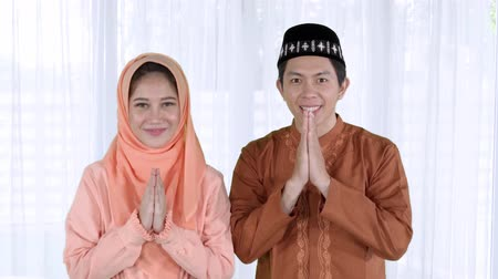 perdão : Attractive young muslim couple wearing islamic clothes and showing a muslim greeting hands at home during Eid Mubarak. Shot in 4k resolution