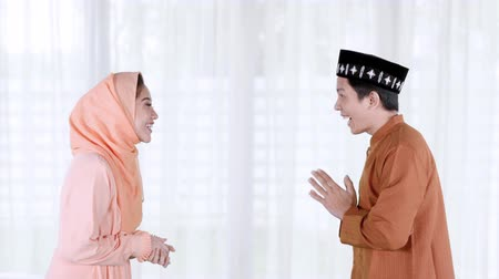 perdão : Happy young muslim couple giving a muslim greeting hand gesture to each other during Eid Mubarak at home. Shot in 4k resolution