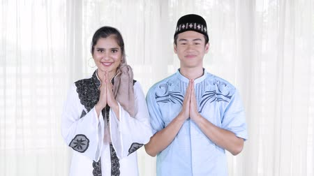 perdão : Young muslim couple smiling and showing a greeting hands gesture while wearing islamic clothes during Ramadan Kareem or Eid Mubarak at home. Shot in 4k resolution