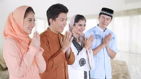 saudação : Young muslim people congratulate Eid Mubarak day with a greeting hand gesture and wearing islamic clothes at home. Shot in 4k resolution