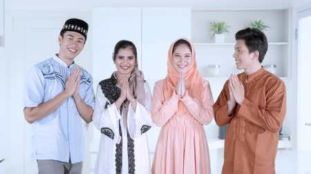 традиции : Group of young muslim people showing a greeting hands while wearing islamic clothes at home. Shot in 4k resolution Стоковые видеозаписи