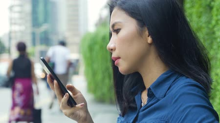 beira da estrada : Side view of attractive young woman using a mobile phone while standing on the sidewalk. Shot in 4k resolution