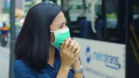 ношение : JAKARTA, Indonesia - April 24, 2019: Air Pollution Concept. Young woman standing on the roadside while wearing a mask to protect from air pollution. Shot in 4k resolution