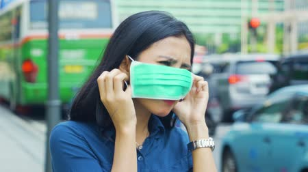 vestindo : Air Pollution Concept. Young woman standing on the street and wearing a mask after coughing to protect from air pollution. Shot in 4k resolution Vídeos