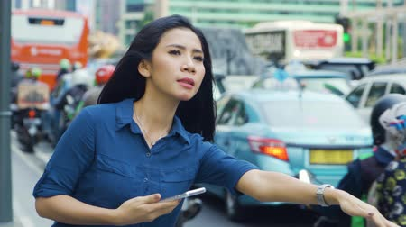 stopping : JAKARTA, Indonesia - April 24, 2019: Young woman waiting online transportation while holding a mobile phone on the street. Shot in 4k resolution Stock Footage