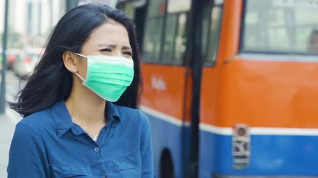 ношение : Air Pollution Concept. Young woman wearing a face mask on the street while waiting a bus. Shot in 4k resolution