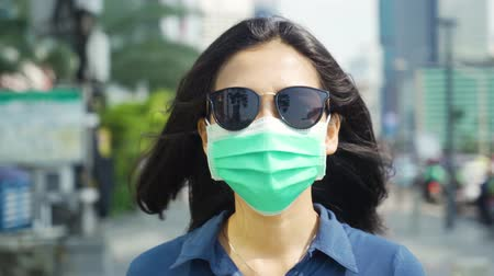 çevre koruma : Air Pollution Concept. Young woman wearing a mask and sunglasses while walking on the sidewalk in the city. Shot in 4k resolution