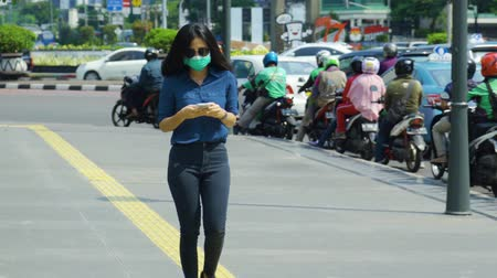 ношение : JAKARTA, Indonesia - April 24, 2019: Air Pollution Concept. Young woman wearing a mask while walking on the sidewalk and using a mobile phone. Shot in 4k resolution Стоковые видеозаписи