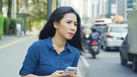 использование : JAKARTA, Indonesia - April 24, 2019: Young woman holding a mobile phone while waiting online transportation on the sidewalk. Shot in 4k resolution