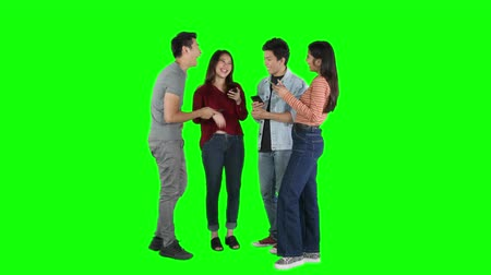 fulllength : Group of young people standing in the studio while talking and using mobile phones. Shot in 4k resolution with green screen background