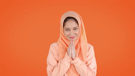 perdão : Beautiful young muslim woman wearing headscarf and showing a greeting hand gesture. Shot in 4k resolution with orange background Vídeos