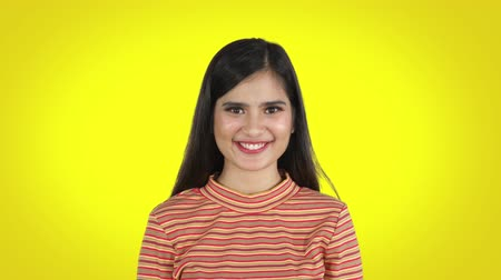 feliz : Pretty young woman looking and smiling at the camera while standing in the studio against yellow background. Shot in 4k resolution