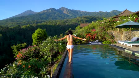 walking back : Back view of young woman walking on the poolside while wearing swimsuit with beautiful mountain view in Lombok near Bali, Indonesia. Shot in 4k resolution