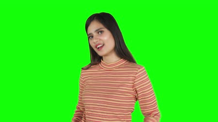 zöld : Pretty young Asian woman posing in the studio while looking and smiling at the camera. Shot in 4k resolution with green screen background Stock mozgókép