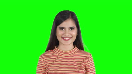 zöld : Portrait of beautiful young woman looking and smiling at the camera in the studio. Shot in 4k resolution with green screen background